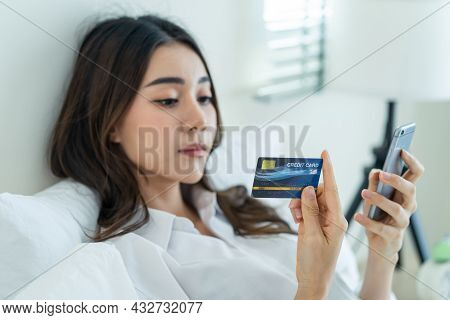 Asian Attractive Woman Enjoy Shopping Online On Bed At Home In Morning. Casual Female Lying In Bedro