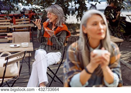 Senior Cafe Guests, Focus On Silver Haired Woman With Glasses Recording Audio Message