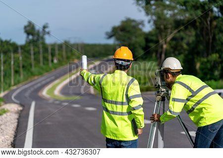 Teamwork Of Surveyor Engineers Worker Making Measuring With Theodolite On Road Works. Survey Enginee
