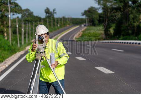 Asian Surveyor Engineer Worker Making Measuring With Theodolite On Road Works. Survey Engineer At Ro