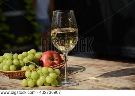 A Glass Of White Wine With Grapes On Wooden Table. White Wine Riesling, From White Grapes