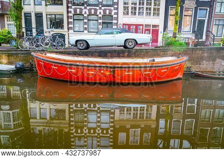 Amsterdam Holland - August 19 2017; Vintage Orange Color Canal Boat Moored Alongside With White Amer