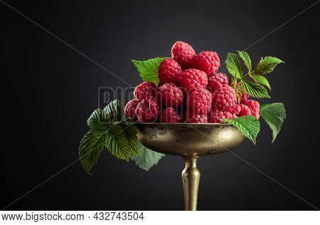 Fresh Raspberries With Leaves In An Old Brass Dish On A Black Background.