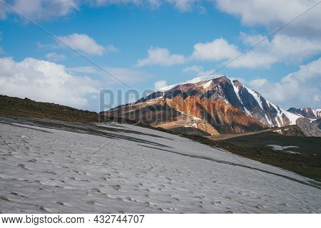 Scenic Alpine Landscape With Snow-capped Mountain Peak And Vivid Red Sharp Rocks Under Blue Sky With
