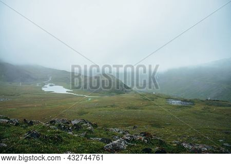 Atmospheric Alpine View To Beautiful Mountain Lake Among Hills During Rain. Scenic Landscape With Sn