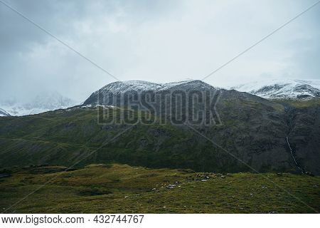 Minimalist Alpine Landscape With Snowy Mountains In Low Cloud In Overcast Weather. Deep Gorge On Bac