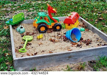 Forgotten Toys In The Sandbox Outside. Children Playground Outdoors