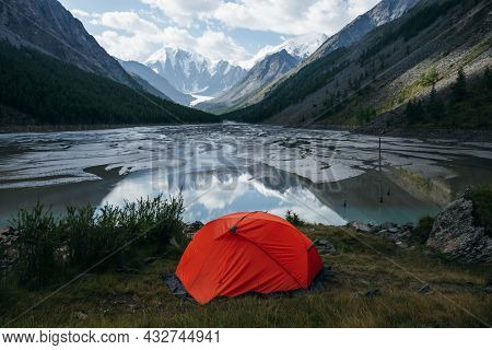 Scenic Alpine Landscape With Orange Tent Near Beautiful Mirror Mountain Lake With Streams In Highlan