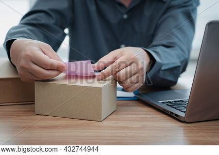 A Man Sticking Notes On The Parcel Box Follow Order List In Stock From Computer : Online Order Conce