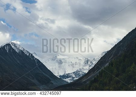 Atmospheric Landscape With Great Snow Mountains Under Cloudy Sky. Dramatic Scenery With Trees On Hil