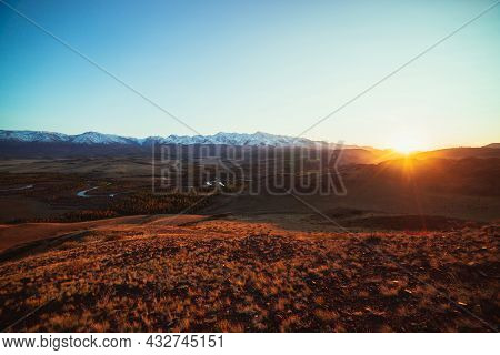 Awesome Autumn Landscape With Mountain River In Forest Valley And Great Snow-covered Mountain Range