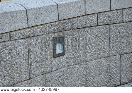 Stone Wall Of Regular Granite Roughly Hewn Blocks With A Hidden Lamp To The Wall Surface. It Shines