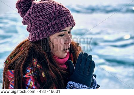 A Girl In A Bright Warm Ski Suit Is Freezing, Blocks Of Ice On The Background