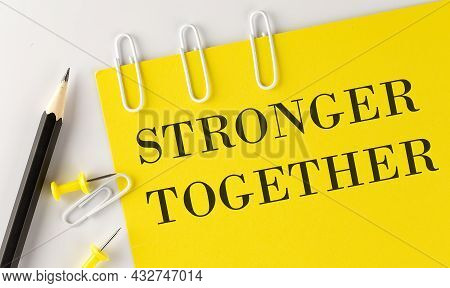Stronger Together Word On The Yellow Paper With Office Tools On The White Background