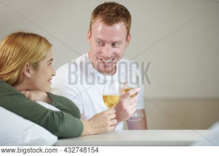 Joyful Young Boyfriend And Girlfriend Clinking Champagne Glasses When Spending Evenig At Home