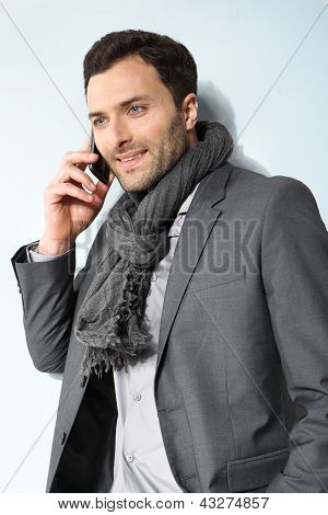 Young businessman using cell phone, over grey background