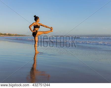 Yoga Practice On The Beach. Utthita Hasta Padangusthasana, Extended Hand-to-big-toe Pose. Standing B