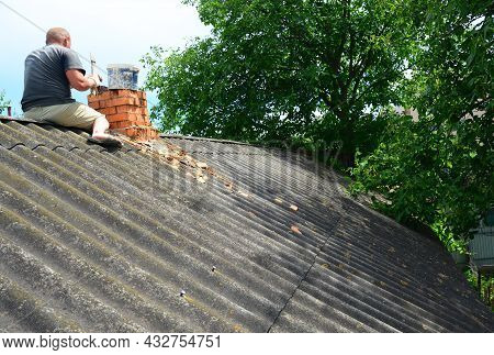 Brick Chimney Repair. A Roofer On An Asbestos Roof Is Replacing Cracked Bricks, Building A New Brick