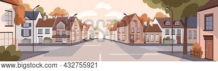 City Street At Sunset In Summer. Town Panorama With Road, Sidewalk, Houses In Urban Residential Dist