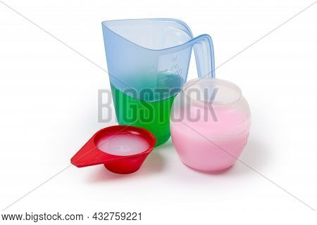 Various Liquid Laundry Detergents Are Poured In The Different Plastic Measuring Cups And Scoop On A