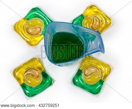 Blue Transparent Plastic Measuring Cup With Green Liquid Laundry Detergent Among The Colored Laundry