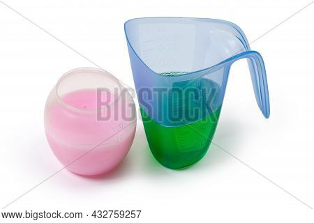Two Various Liquid Laundry Detergents Are Poured In The Different Plastic Measuring Cups On A White