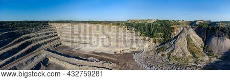 Slopes Of Operating Granite Quarry With Mining Equipment On Ledges, Waste Rock Dumps In Summer Morni