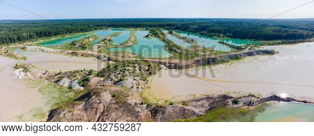 Colored Lakes Among Old Waste Rock Dumps Arisen On The Site Of The Abandoned Ilmenite Quarry Against