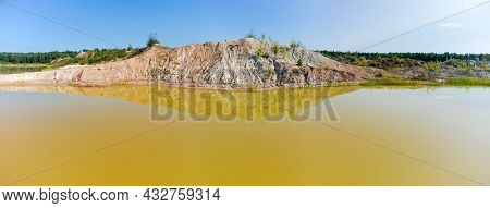 Lake With Yellow Water Against The Old Waste Rock Dumps Arisen On The Site Of The Abandoned Ilmenite