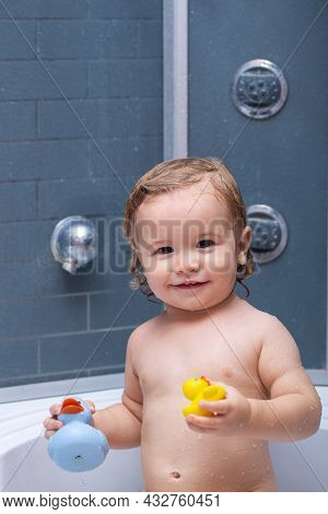 Child In Shower. Happy Baby Taking A Bath Playing With Foam Bubbles. Little Child In A Bathtub. Smil