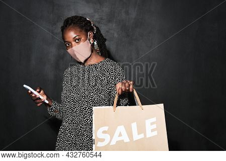 Portrait Of African Young Woman In Protective Mask Doing Shopping Online On Mobile Phone During Pand