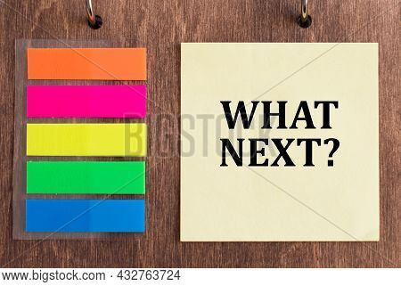 What's Next, The Phrase Is Written On A Yellow Card Against A Wooden Background Next To Colorful Not