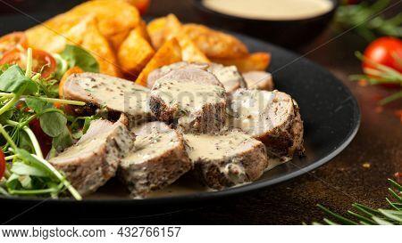 Roast Pork Tenderloin In Mustard Gravy With Vegetables And Potato Wedges