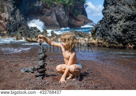 Kid Making Stack Stones On The Coast Of The Sea In The Nature. Cairn On The Ocean Beach, Five Pebble