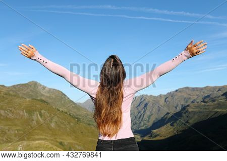 Back View Of Woman Outstretching Arms Celebrating Vacation In The Mountain