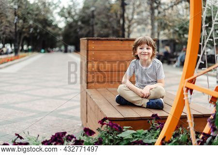 Smiling Kid Sitting On A Wooden Bench In The City Park. Urban Child Boy Weekend. Autumn Outdoors Lei
