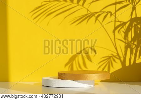 White And Gold Cylindrical Scenes On A White Table On A Yellow Background With A Shadow Of Palm Leav
