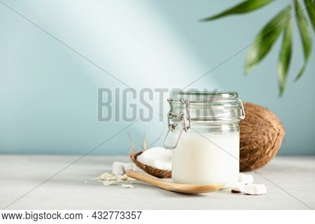 Coconut oil in jar with fresh coconut and tropical leaves, Spa cosmetic and food ingredient, space for text