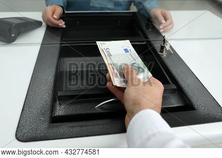 Cashier Giving Money To Woman At Currency Exchange Window In Bank, Closeup