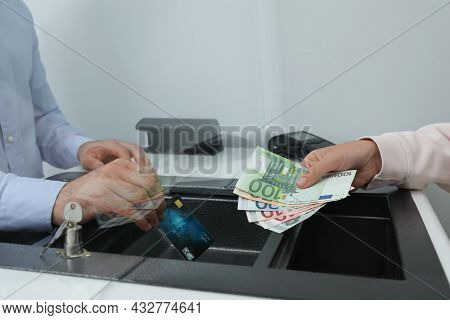 Woman Putting Money On Card In Bank, Closeup. Currency Exchange