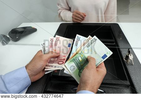 Cashier With Money At Cash Department Window, Closeup. Currency Exchange