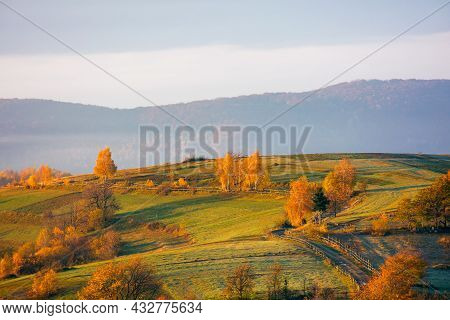 Mountainous Rural Landscape At Sunrise. Trees And Fields In Morning Light. Mist In The Distant Valle