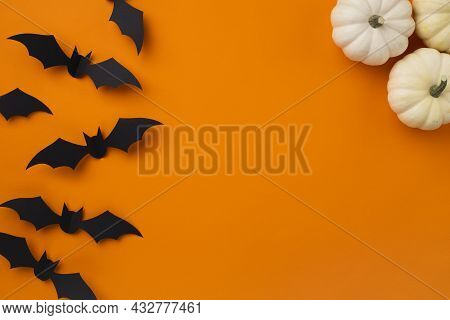 Happy Halloween Holiday Concept. Halloween Decorations, Pumpkins And Bats On Orange Background. Hall