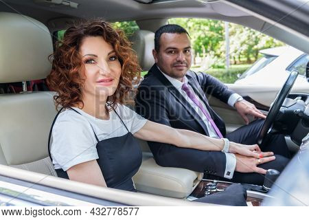 Loving Couple In A Car Loving Couple In The Car Hold Hands. Middle Eastern Man In A Business Suit Wi