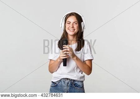 Attractive Smiling Brunette Girl In Headphones, Singing Karaoke, Holding Microphone
