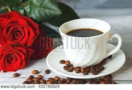 White Cup Of Coffee, Coffee Beans And Red Roses On Light Gray Background. Romantic Breakfast Concept