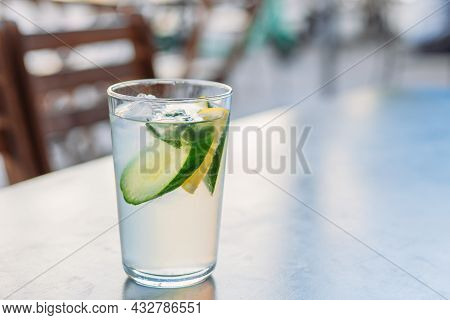 Lemonade With Lemons And Cucumber On Black Table Over City Background. Glass Of Cold Drinks. Concept