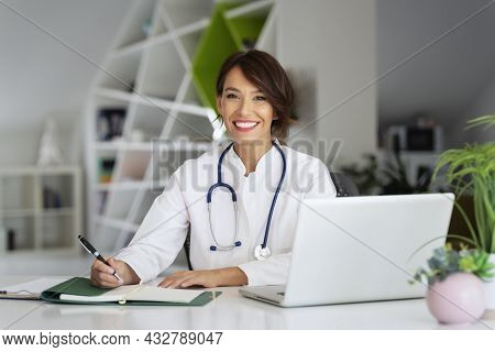 Smiling Female Healthcare Worker Doing Some Paperwork And Using Laptop While Working At Doctor's Off