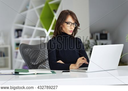 Attractive Businesswoman Wearing Turtleneck Sweater While Working On Laptop At The Office