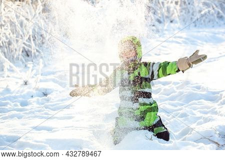A child plays in the snow in winter. Winter scene with a child. Happy childhood. Christmas happiness.
